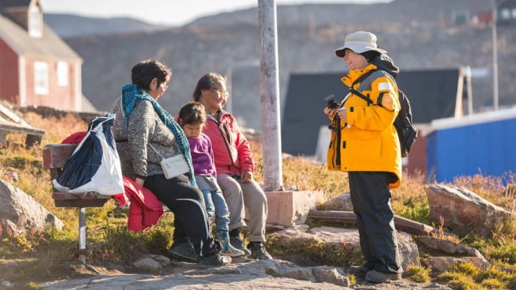 Locals from an inuit village in greenland sit on a bench in a village with colorful houses in the arctic circle