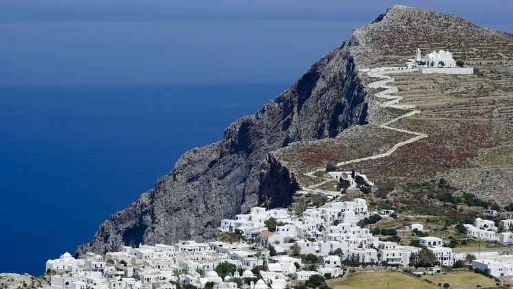 A town of white buildings with a zig-zagging path up the hill to the church on the island of folegandros on the aegean sea in greece