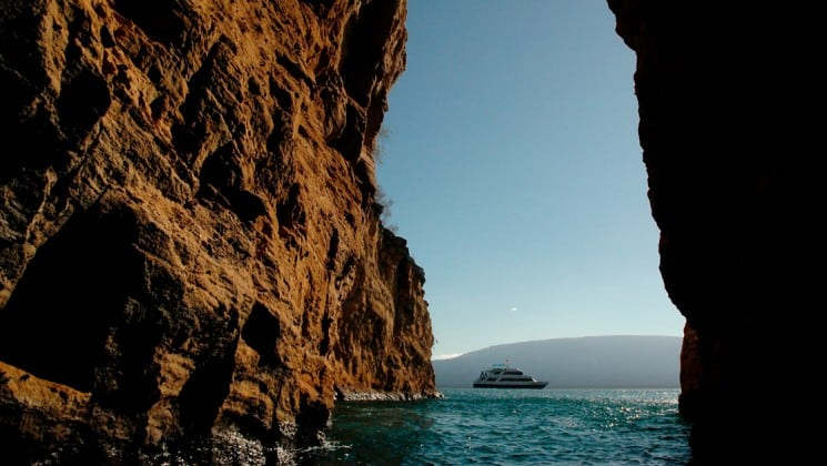 The letty yacht passes between two rock outcroppings on the ocean at the galapagos islands