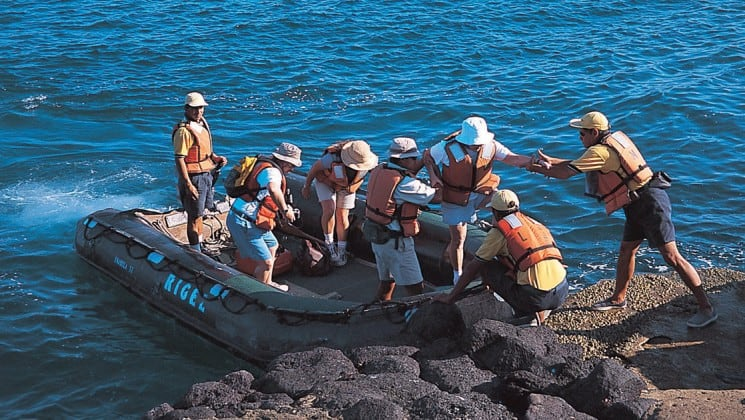 Guests at La Pinta cruise ship disembark from a motored raft for a full-day of wildlife viewing at the Galapagos Islands