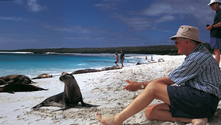 A man sits on a white sand beach and holds his hand out toward a sea lion while traveling aboard the La Pinta luxury cruise ship through the Galapagos Islands