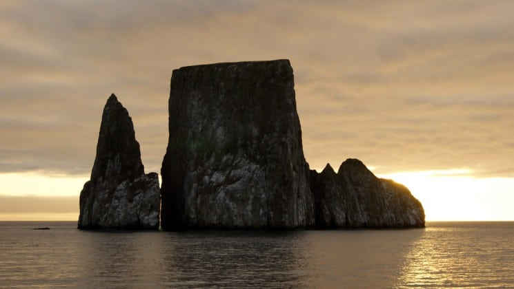 golden light from the sunset silhouettes rocks rising from calm waters at the galapagos islands