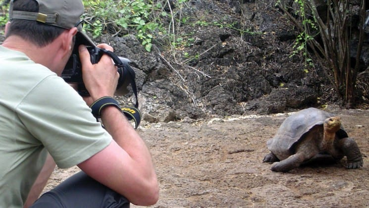 A man holds his camera to take a photo of a tortoise crawling across a rocky surface at the Galapagos Islands