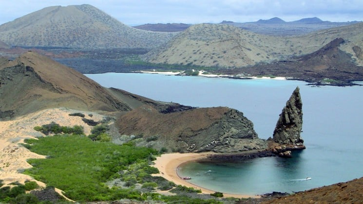 An aerial view of Pinacle Rock, a destination visited by Isabella Cruises in the Galapagos Islands, with a pointed cliff jutting out of the water at the edge of an inlet marked with a sandy beach and a grassy hill.