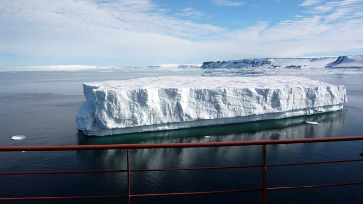 Looking out from the railing of the fifty years of victory ship, an iceberg rises above the ocean in the north pole