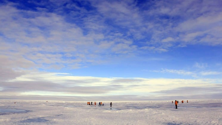 people from the expedition walk across pack ice and a glacier at the north pole
