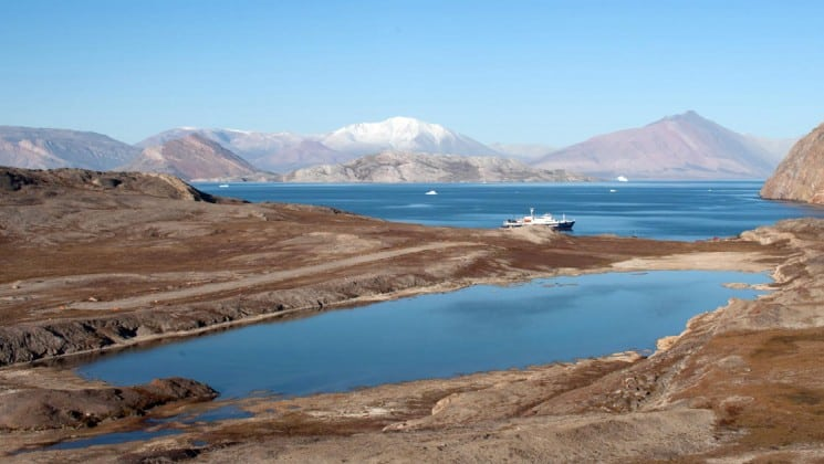 a landscape view of greenland with brown land, blue ocean, and snow-capped peaks