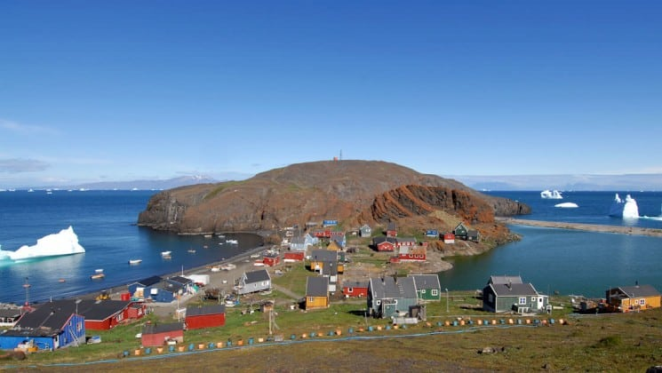 A village is situated on a small island with colorful houses nestled in green pasture in greenland