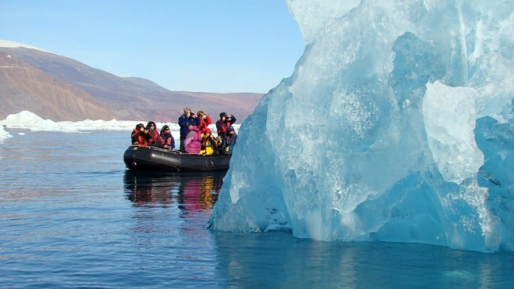 an inflatable boat carries passengers to get a close-up view of an iceberg in greenland at the scoresby sund cruise