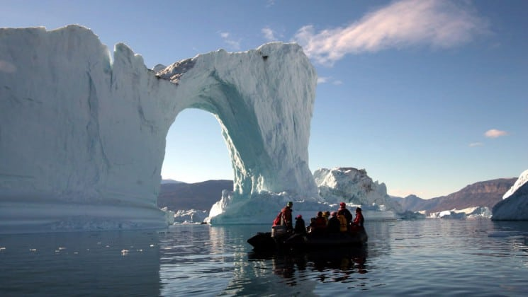 a zodiac boat full of passengers from the scoresby sund adventure cruise get a close look at an iceberg with an arch