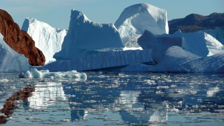 icebergs reflect on water in greenland