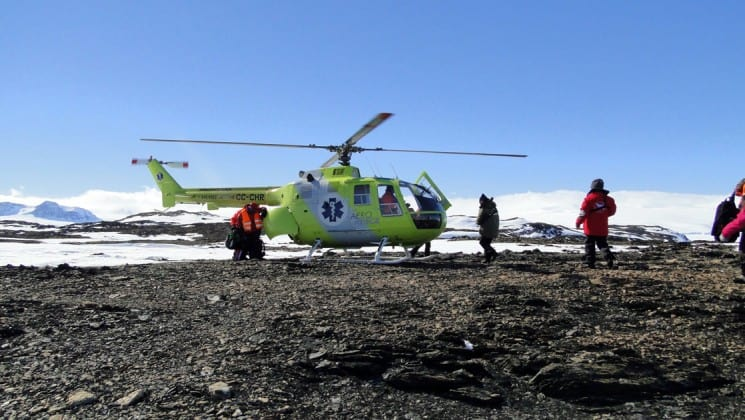 A helicopter lands on a field of rocks with ice and snow in the background, as workers stand by, as part of a tour with weddell sea emperor penguin voyage in antarctica