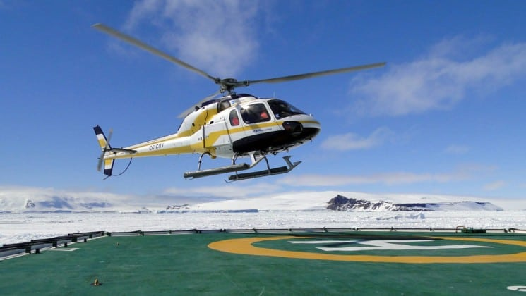 A helicopter lands on a pad surrounded by ice in antarctica, as part of an expedition with weddell sea emperor penguin voyage luxury cruise