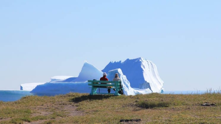 a person sits on a bench on the tundra in the arctic circle, looking at an iceberg in the distance