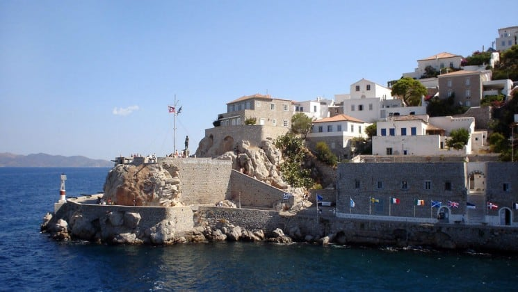 Looking up the hillside from the mediterranean ocean in hydra, with stone walls and white buildings terraced on the slope