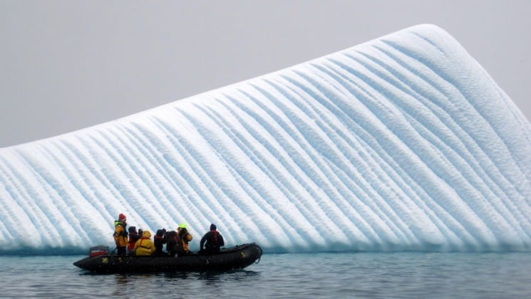 A zodiac full of guests from the antarctica air cruise passes in front of a pyramid shaped iceberg