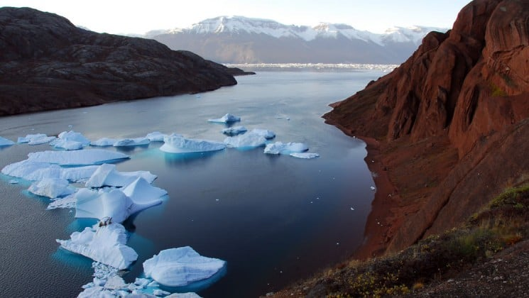 icebergs rise out of the ocean with snow-capped mountains in the distance in greenland
