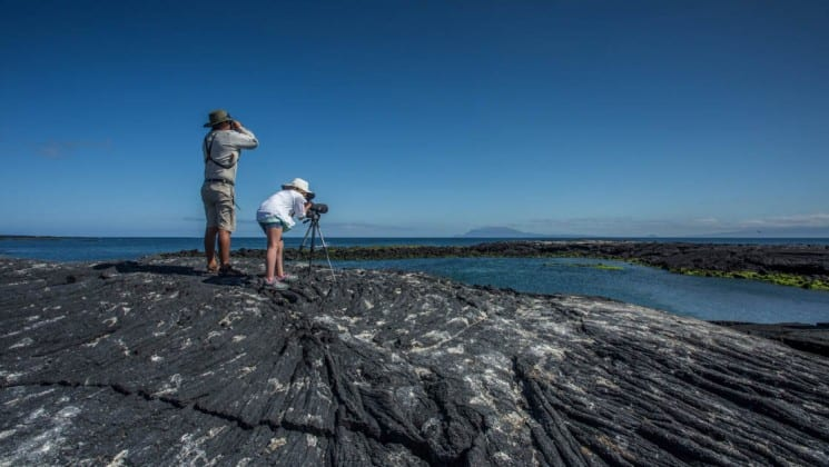 Two passengers of the Isabela luxury yacht set up camera equipment and tripods on lava rocks to photograph the Galapagos Islands.