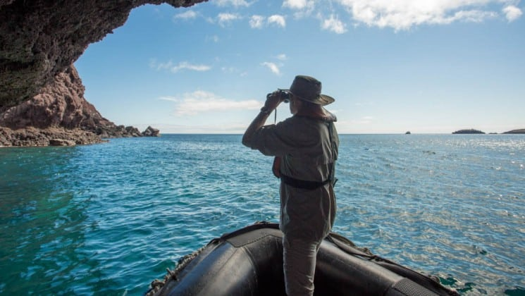 A passenger of the Isabela luxury yacht stands at the edge of a raft and holds binoculars to get a better view of the wildlife on the Galapagos Islands