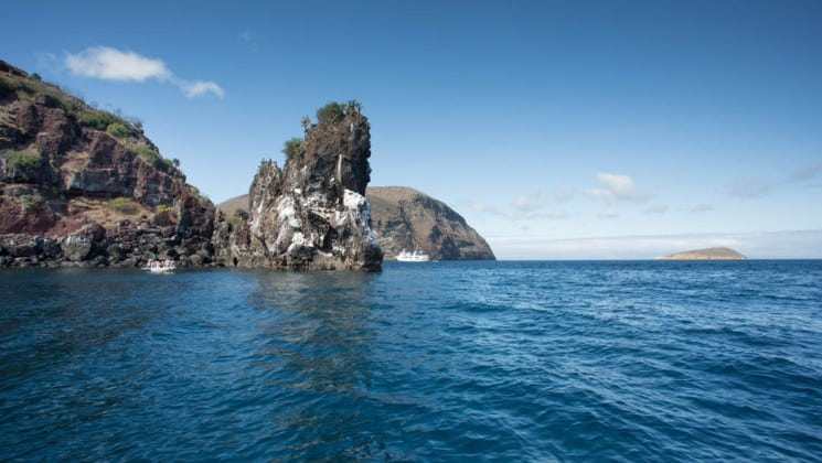 Rocky cliffs jut out of deep blue water along the shoreline of the Galapagos Islands, while cruising through on the Isabela luxury yacht.