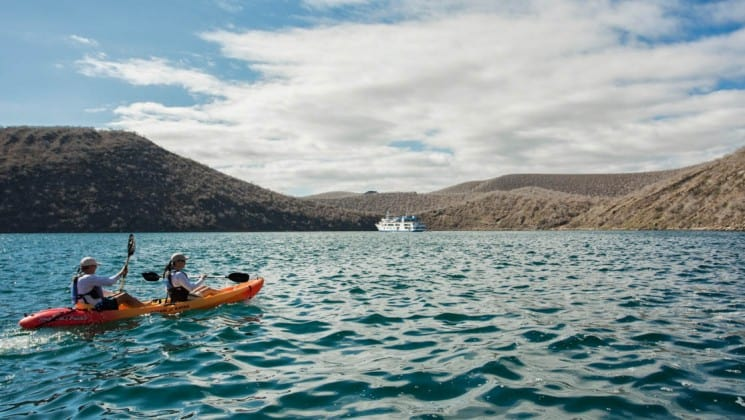 Two people paddle an orange kayak across the ocean with the Isabela luxury yacht anchored in the background at the Galapagos Islands