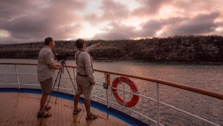 Aboard the Isabela II luxury yacht, a small, intimate cruise in the Galapagos Islands, a couple watches the sunset from the deck balcony.