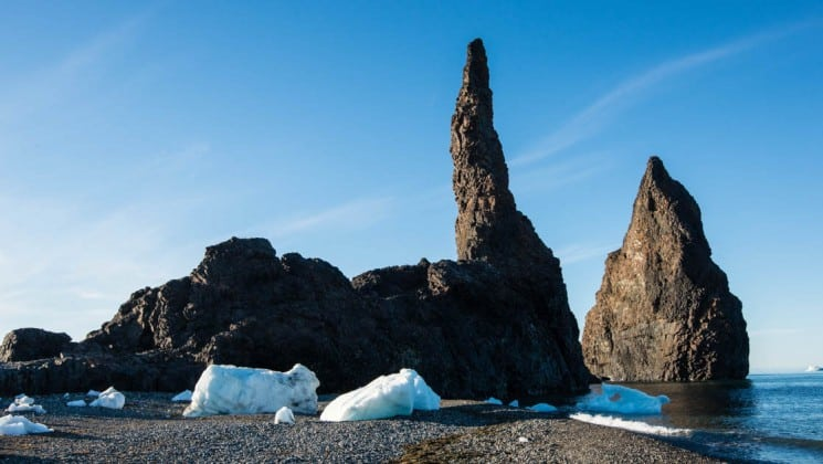 a beach with rock formations and chunks of ice against blue sky in the arctic circle