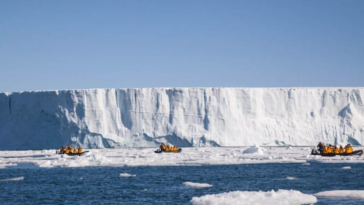 sea kayaks are dwarfed by the size of a glacier and sheer cliff of ice in the arctic