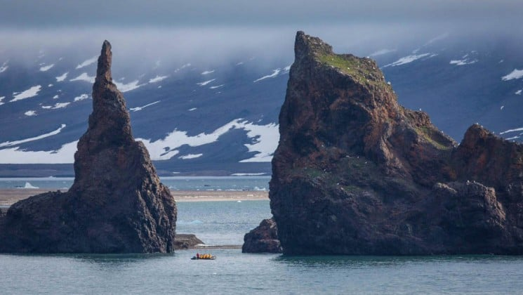 rock formations rise out of emerald blue water with snow-covered mountains in the background in franz josef land in the arctic