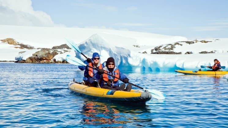 Guests from the National Geographic voyage expedition paddle a kayak near icebergs in antarctica