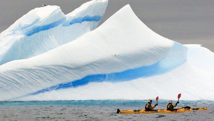 A kayak paddles in the ocean in front of a giant pyramid-shaped iceberg in antarctica