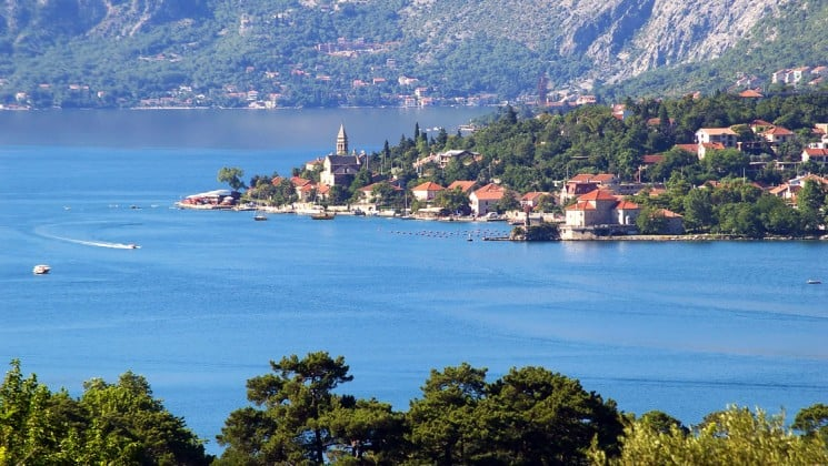 A view looking down the coastline on the adriatic sea with red-tiled roofed towns and lush vegetation