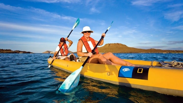 Two people paddle a yellow kayak on a sunny day across the ocean in the Galapagos Islands, while traveling on the National Geographic Islander cruise ship