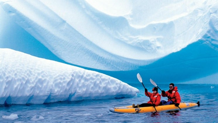 Two kayakers paddle through the ocean just in front of a huge iceberg in antarctica