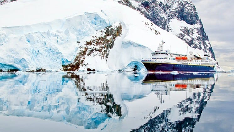 A perfect reflection in still water, the national geographic ship for the white continent voyage is anchored in front of icebergs and rocky peaks