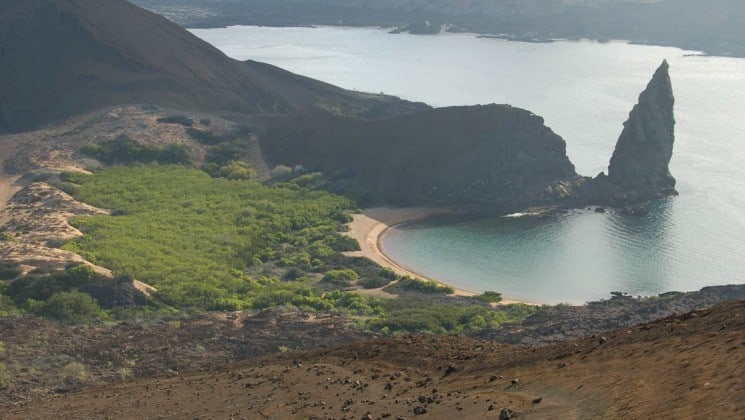 An aerial photo of Bartolome Island in the Galapagos shows a pointed rock and an inlet with grassy slopes and rocky bluffs.