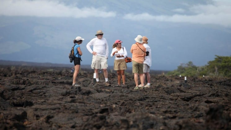 Passengers traveling through the Galapagos Islands aboard the S/S Mary Anne sailing ship take an excursion to land and stand in a group on a rocky bluff before the sea
