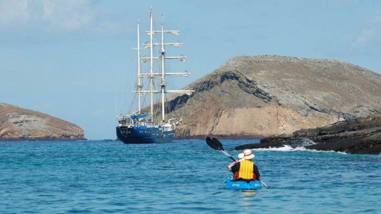 A couple in yellow lifejackets and white hats kayaks across the ocean toward the S/S Mary Anne, a sailing ship anchored next to the Galapagos Islands