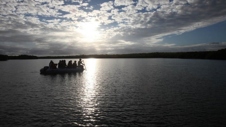 Passengers sit on a panga while a guide paddles across the ocean at sunset, coming back to the S/S Mary Anne sailing ship after an excursion to the Galapagos Islands