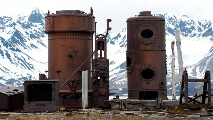 old metal silos used for mining stand on the tundra in the arctic