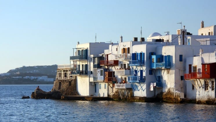 Looking at the town of mykonos with white buildings and greek architecture from the water