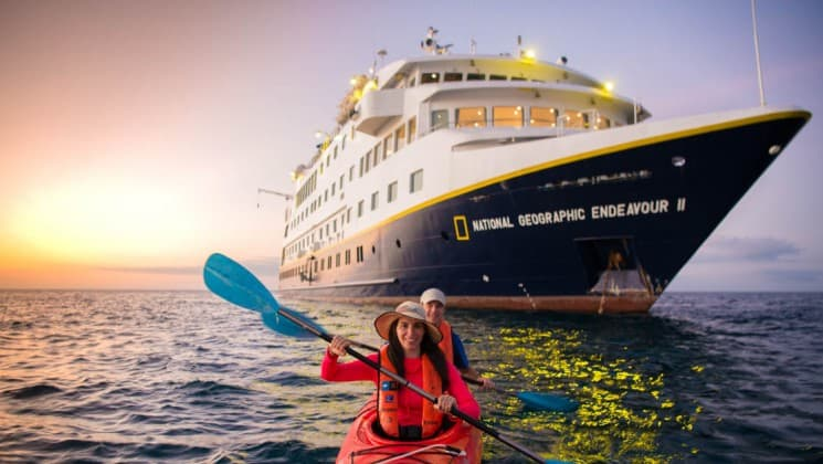Two people kayak on the ocean in front of the large first-class vessel that is the National Geographic Endeavour II, a tailored cruise to explore the Galapagos Islands