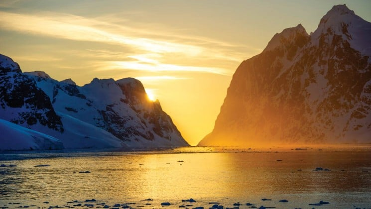 The sunsets, casting golden light on the horizon and the ocean and silhouetting snow-capped mountains in antarctica, on a national geographic epic adventure