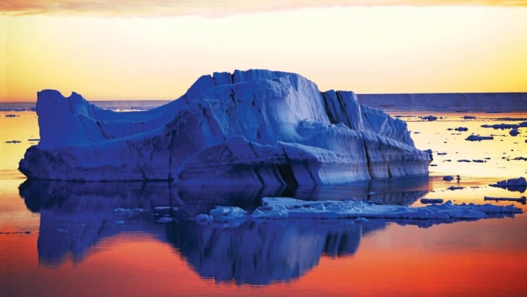 A silhouetted iceberg reflects in calm water, while sunset casts pink and orange hues on the sky and ocean, as seen on a national geographic epic adventure to antarctica