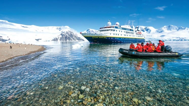 A zodiac boat motors toward the cruise ship that is the national geographic epic antarctica voyage, with icebergs in the background