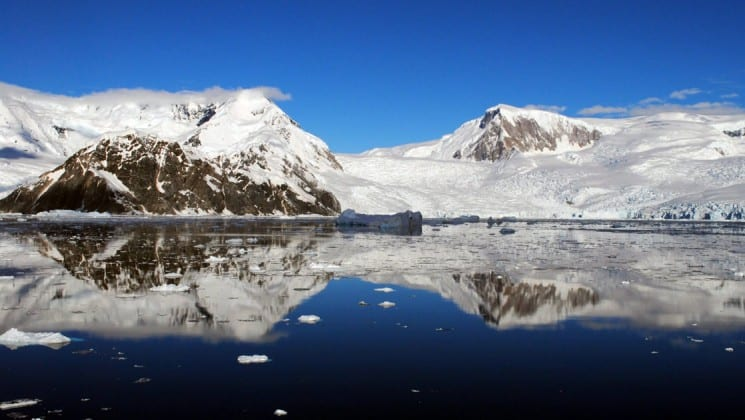 Rocky, snowy mountains are reflected in clear, still water in antarctica's polar circle