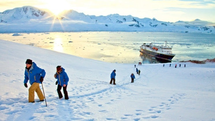 Guests from the national geographic white continent voyage explore neko harbor in the snow while the sun casts golden light over the mountains on the horizon in antarctica
