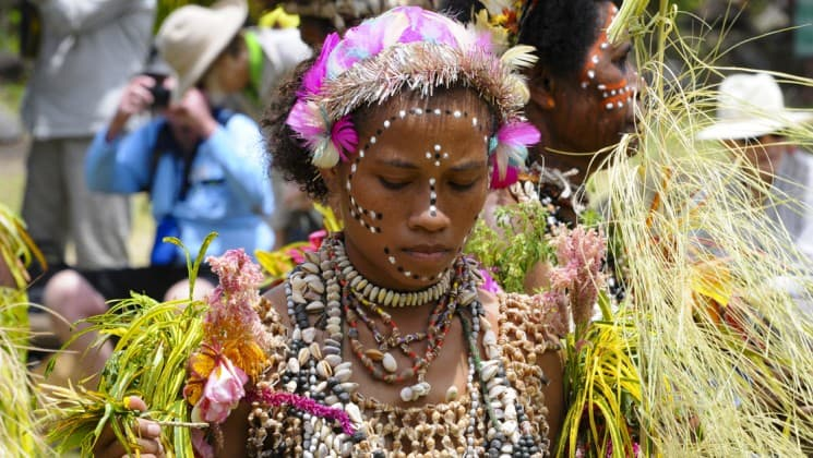 a woman dressed in traditional clothing with floral headwear and ornate makeup in a papua new guinea village in the pacific islands
