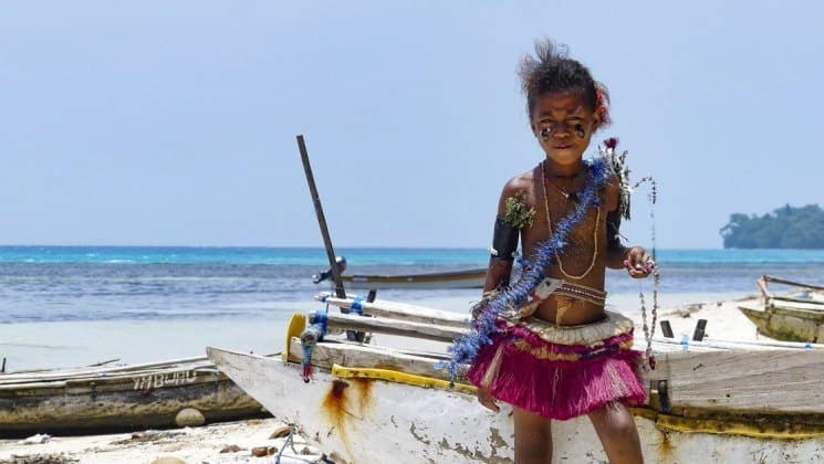 a young person with traditional clothing stands in front of a boat on a white sand beach in papua new guinea in the pacific islands