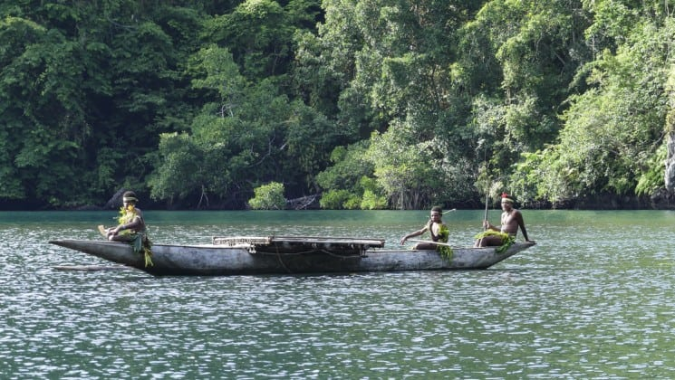 a canoe carved out of wood carries several papua new guinea locals over water in the pacific islands